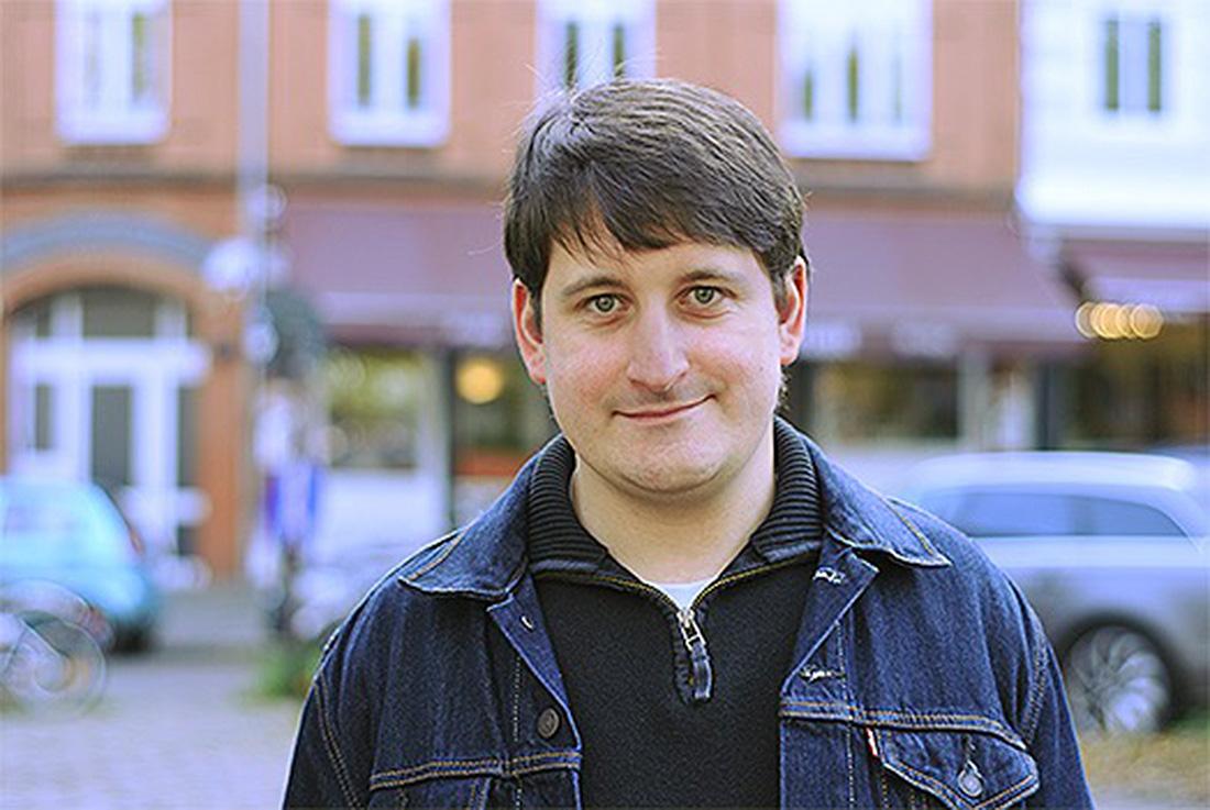 Wolfgang, ein 35-jähriger Mann, steht vor einem Haus und blickt leicht lächelnd in die Kamera.