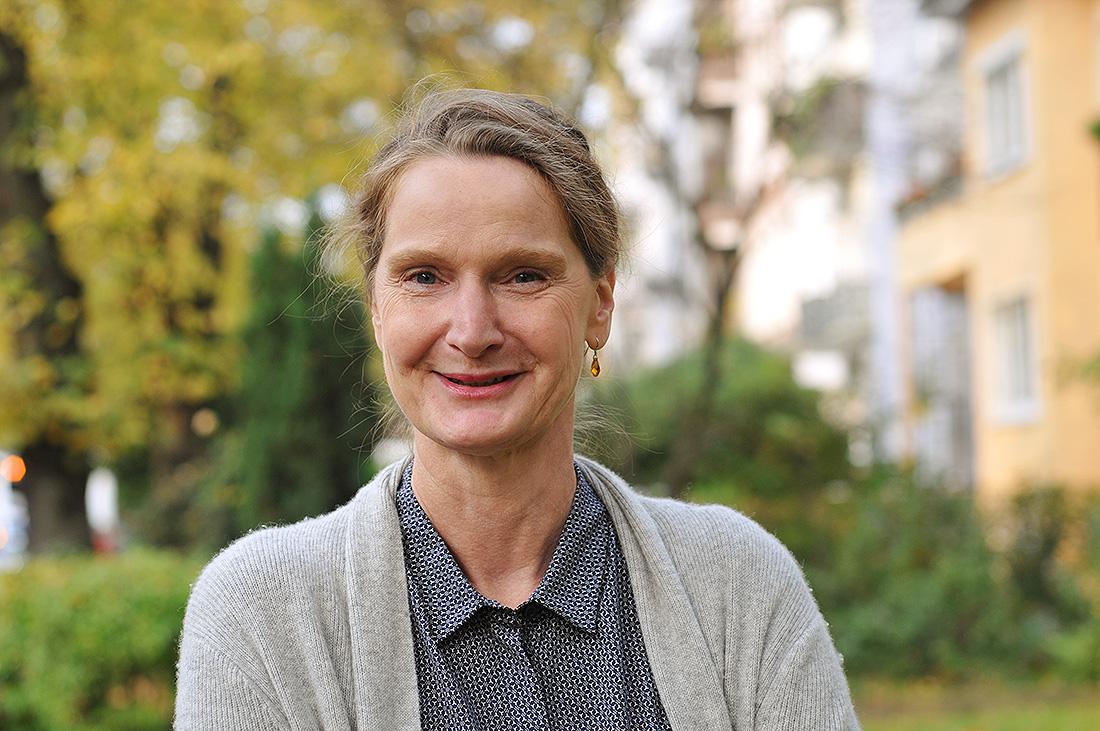 54-jährige Bonni steht in Hamburg vor einem Baum und lächelt.