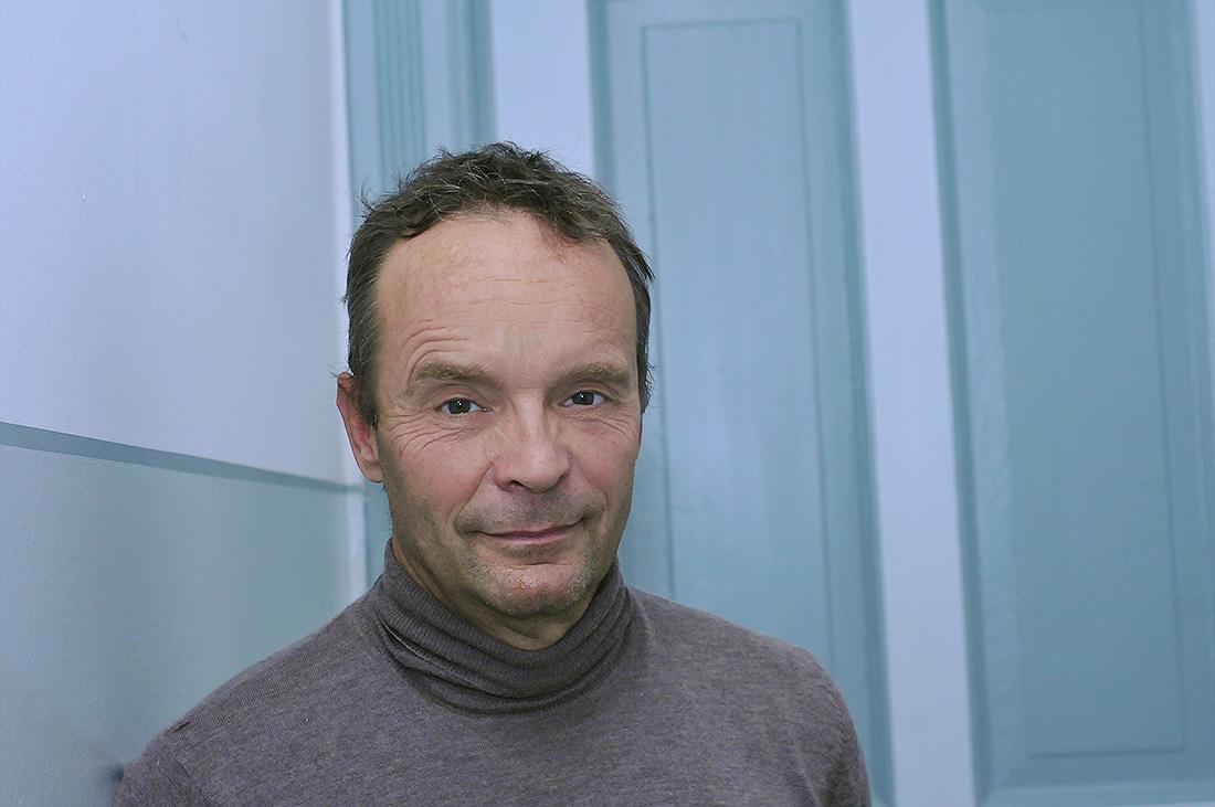 54-jähriger Mann, Hans-Jürgen,, braune Haare, brauner Rolli, guckt leicht lächelnd in die Kamera.