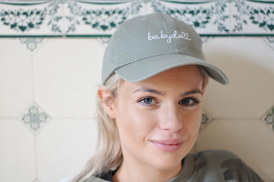 Fabiana sitzt in der Küche, trägt Cap, blickt in die Kamera, lächelt leicht.