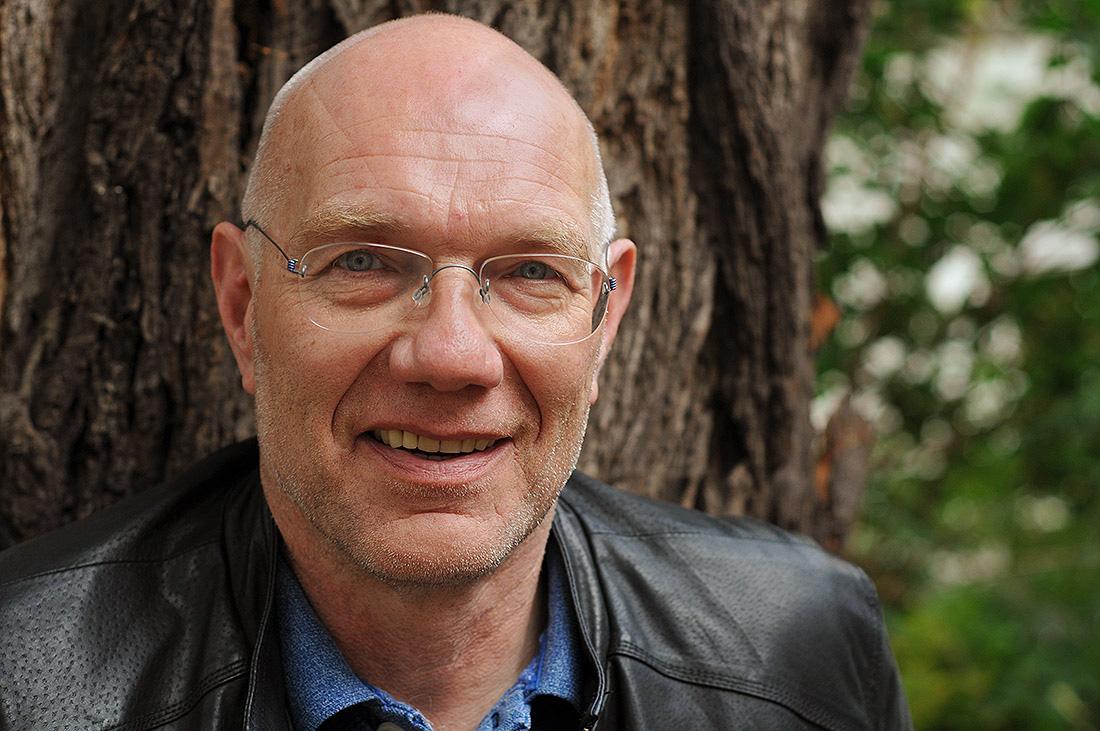 55-jähriger Mann, Heinrich, mit Brille und Glatze steht vor einem Baum.