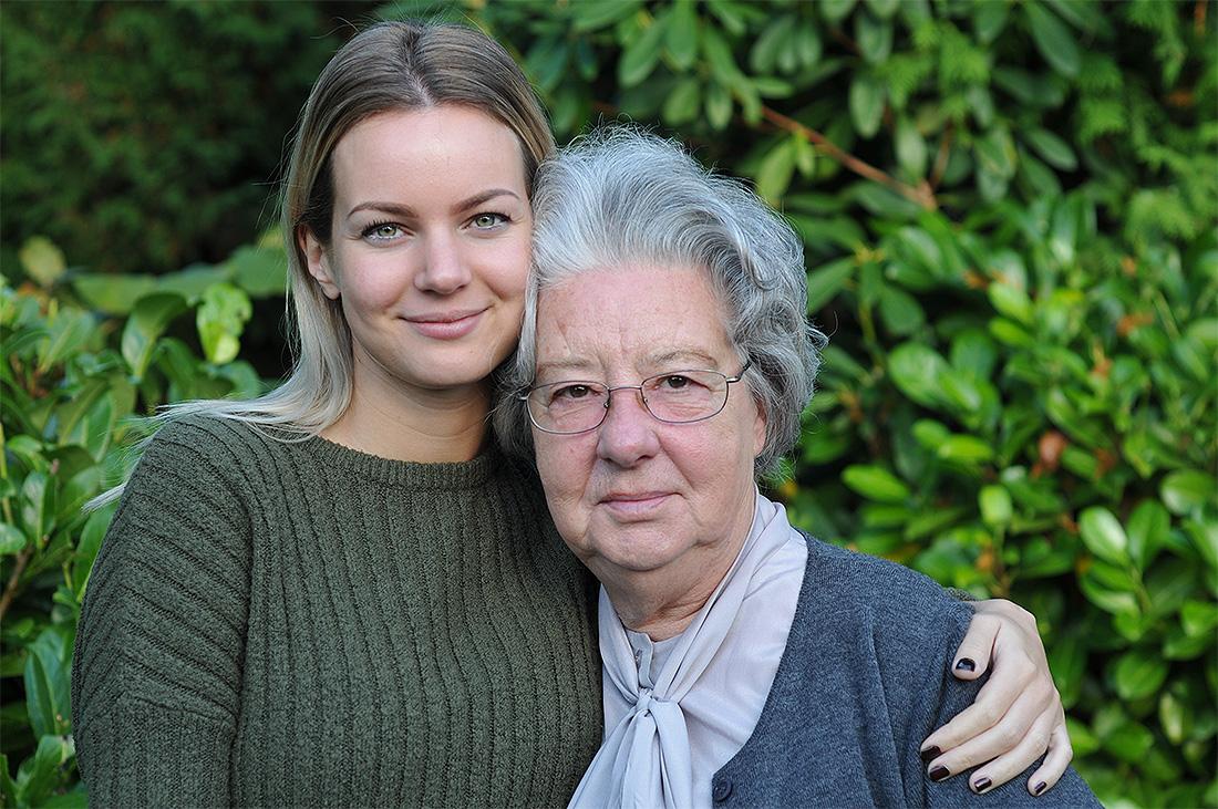 Laura hat Großmutter im Arm, siei sind im Garten.