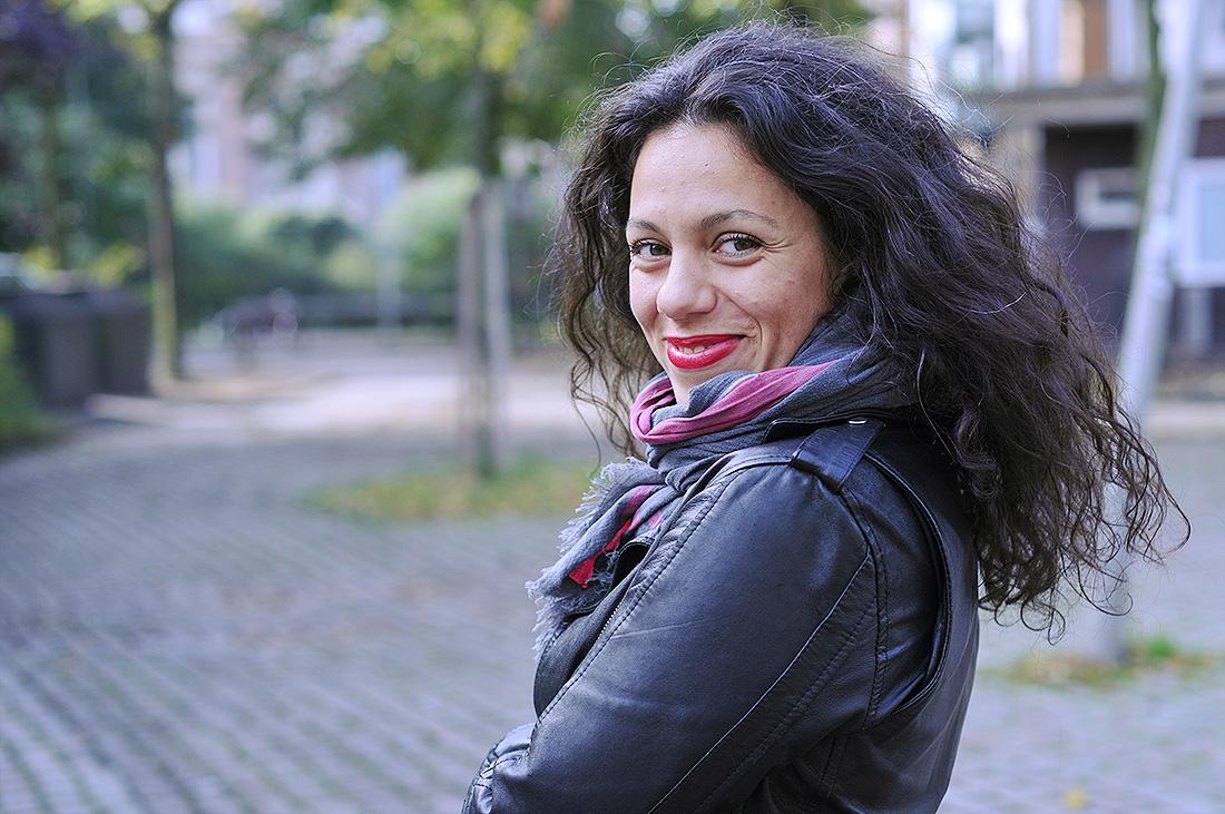 Frau mit langen dunklen Haaren lächelt.