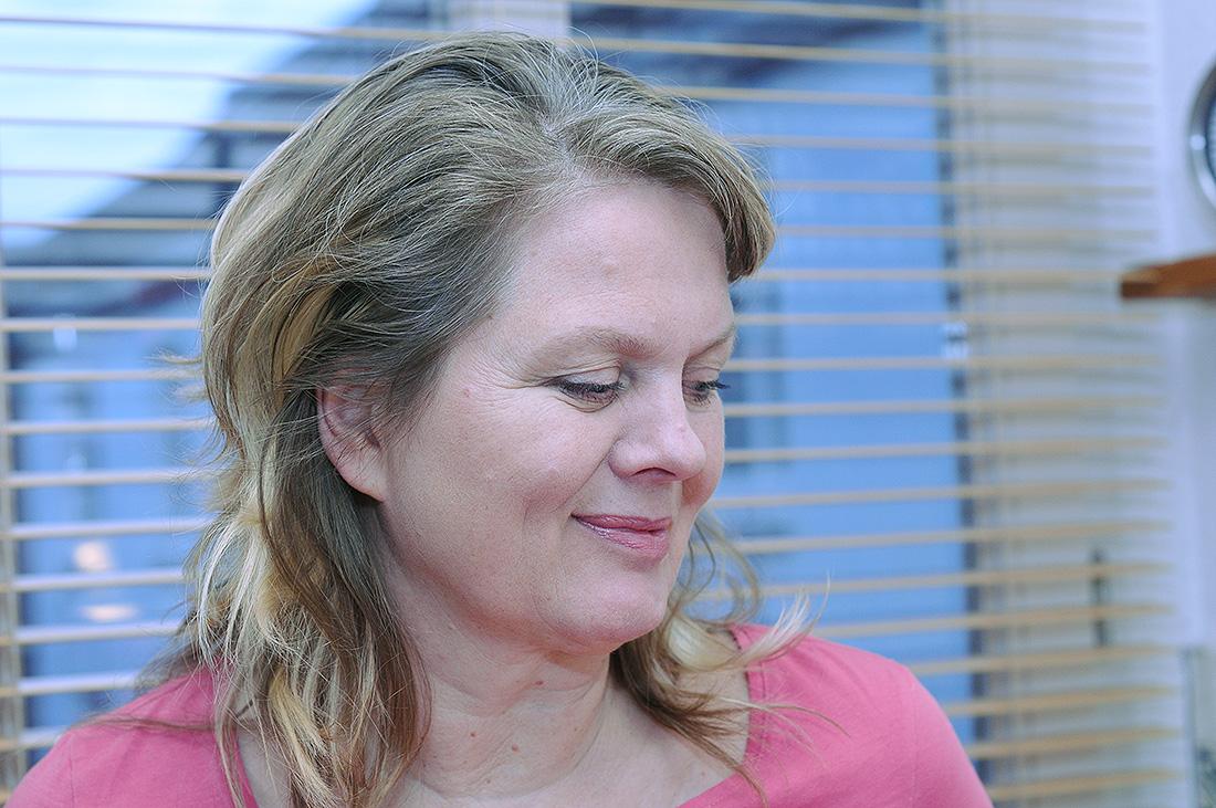 55-jährige Birgit aus Hamburg steht am Küchenfenster, man sieht die Jalousie.
