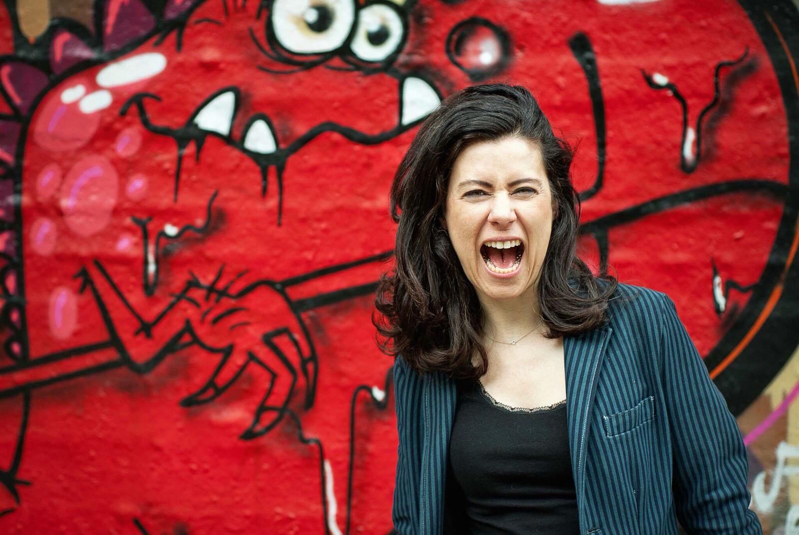 Dunkelhaarige Frau mit weit aufgerissenem Mund: Sie schreit.