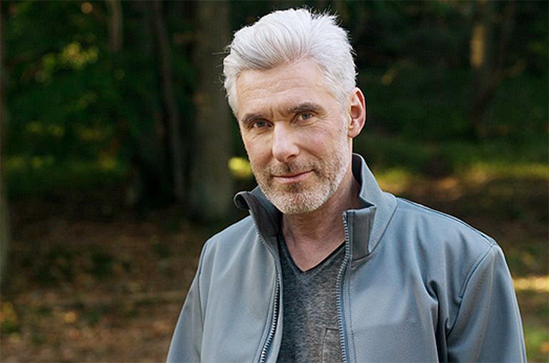 55-jähriger Mann in hellblauer Jacke steht im Park und blickt in die Kamera.